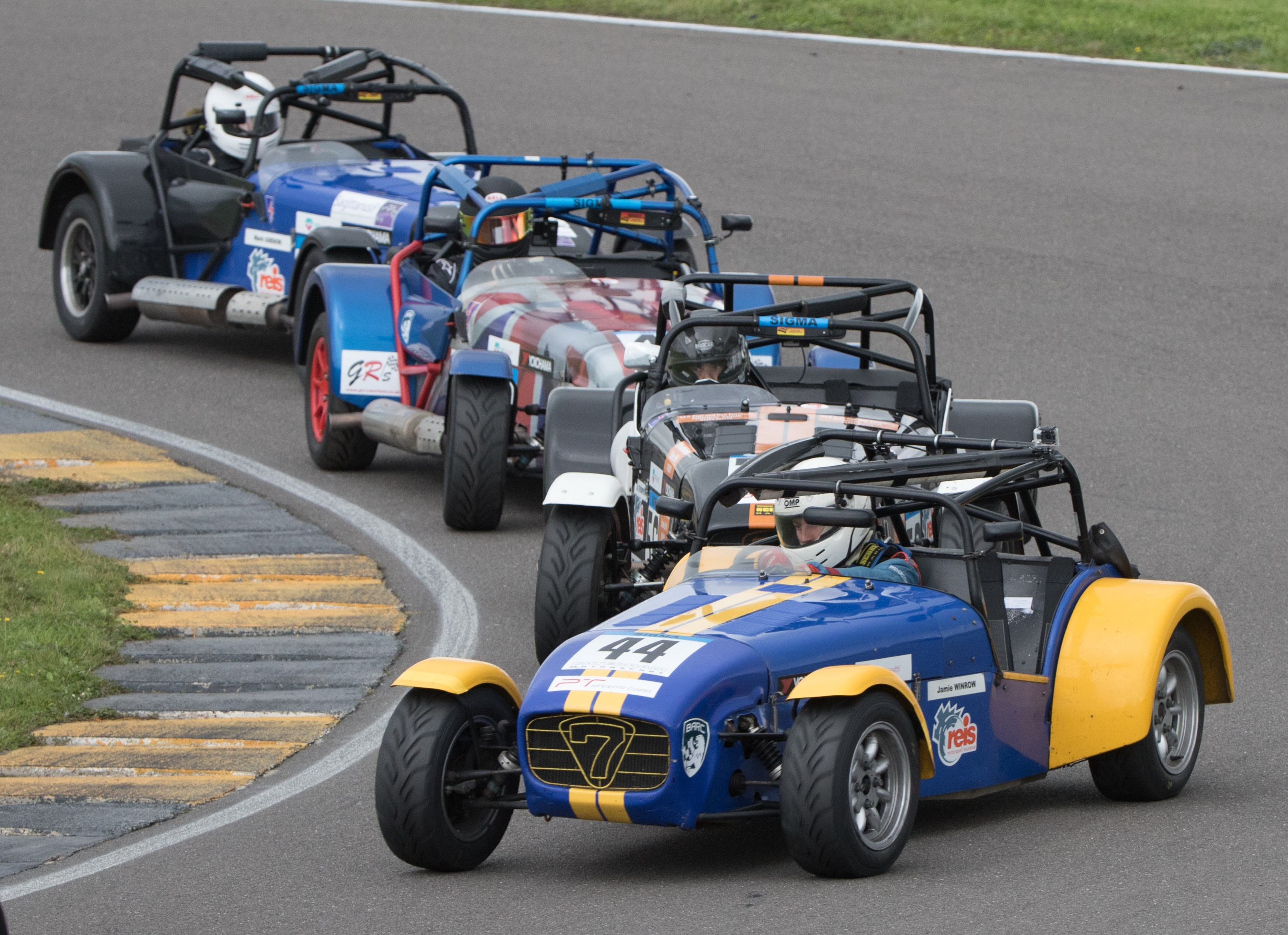 four Caterham 7's going around a track corner