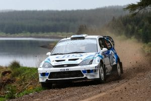 Thorburn racing along gravel track with woodland and lake in the background