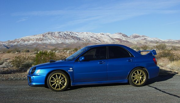 A blue Subaru in front of a mountain back drop