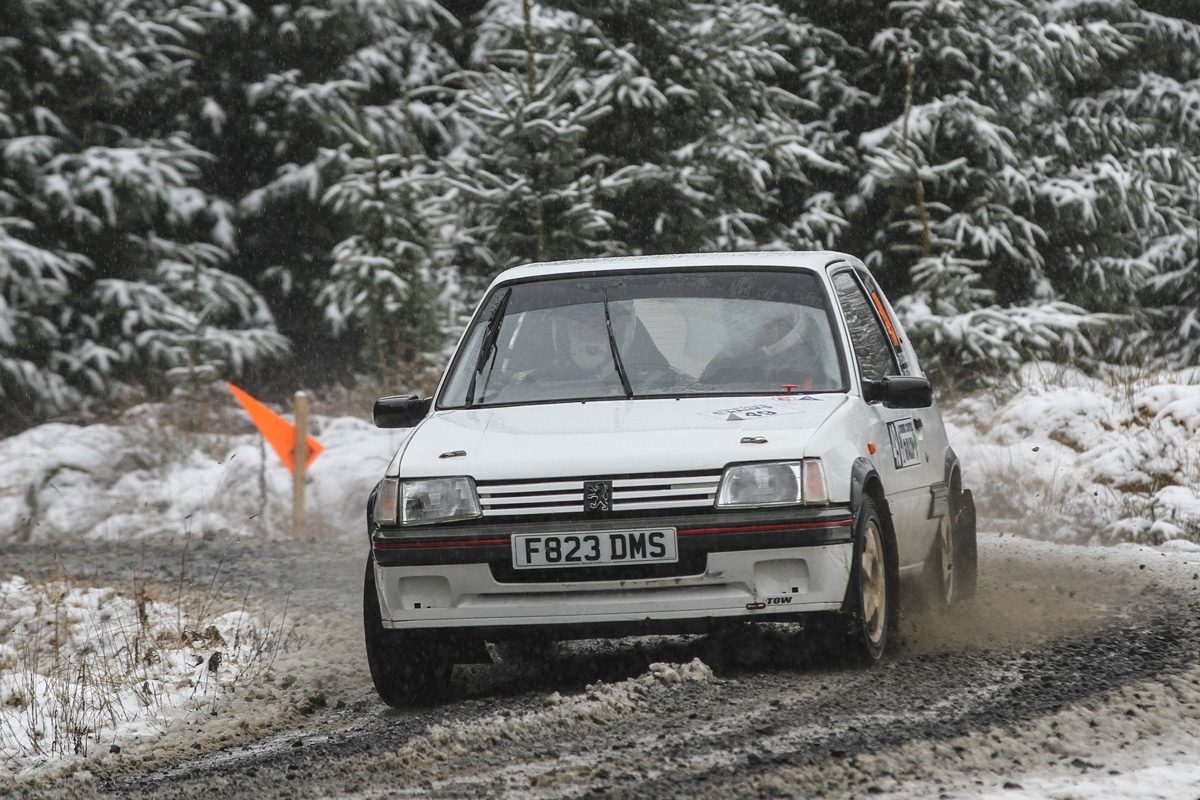 White Peugeot 205 taking a corner at speed on a snowy rally track with fern trees in the background