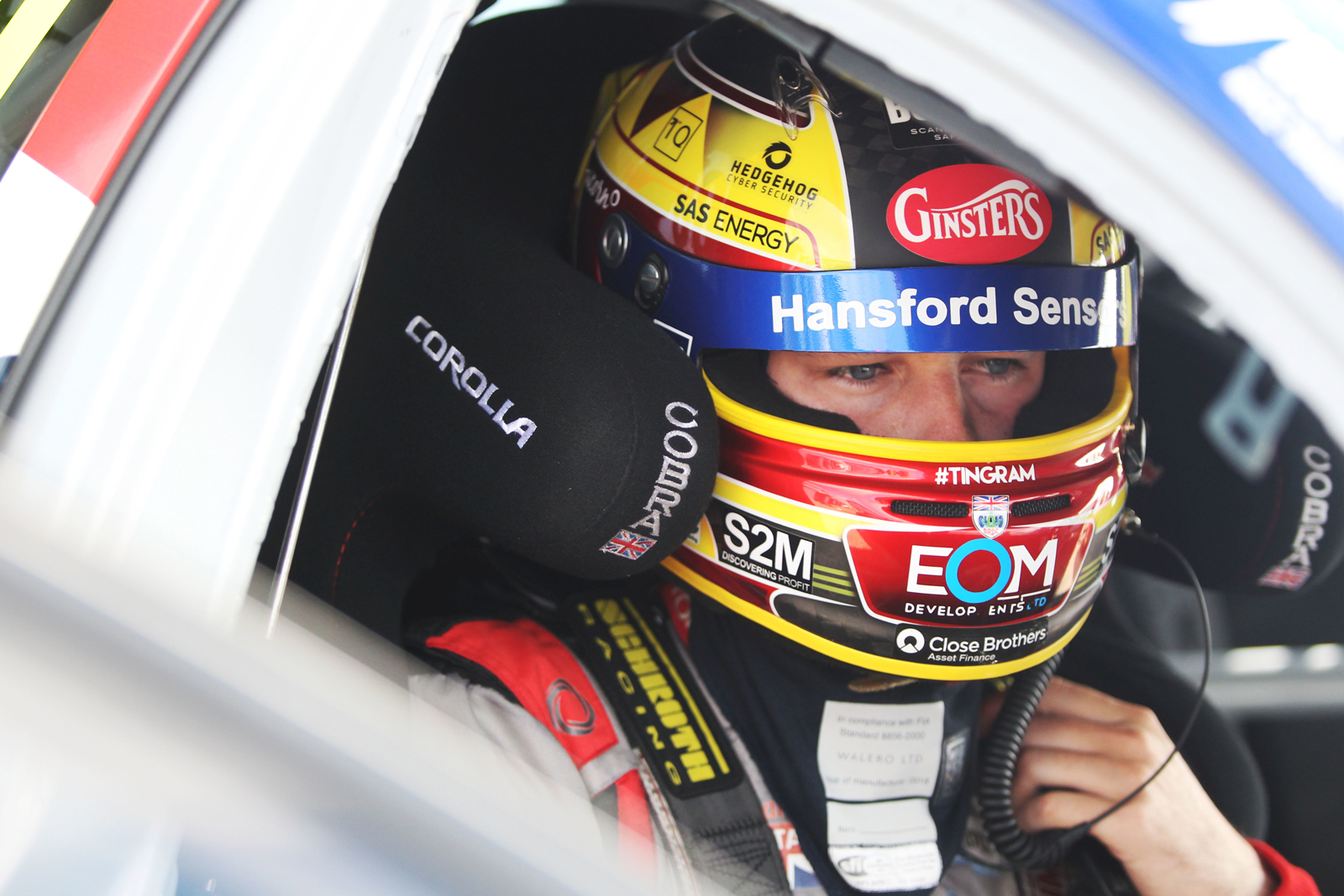 Ingram sitting in car with helmet and gear on ready for race