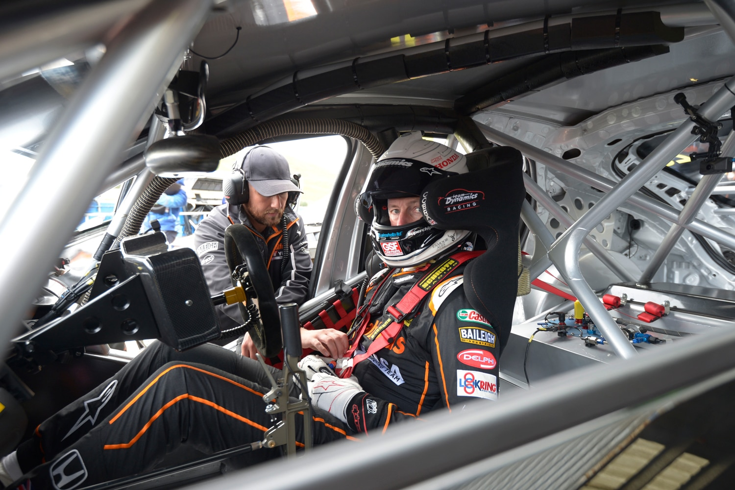 Cammish in his racecar geared up for the race with a team member talking to him through the door