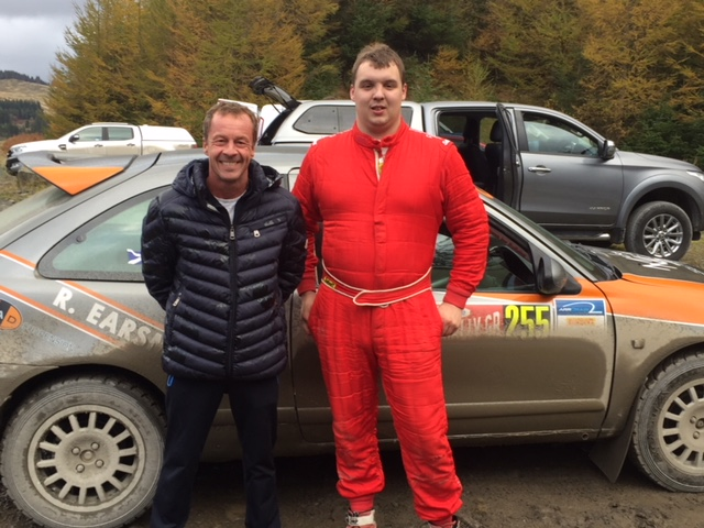 Laukkanen standing with a rally driver in-front of his car