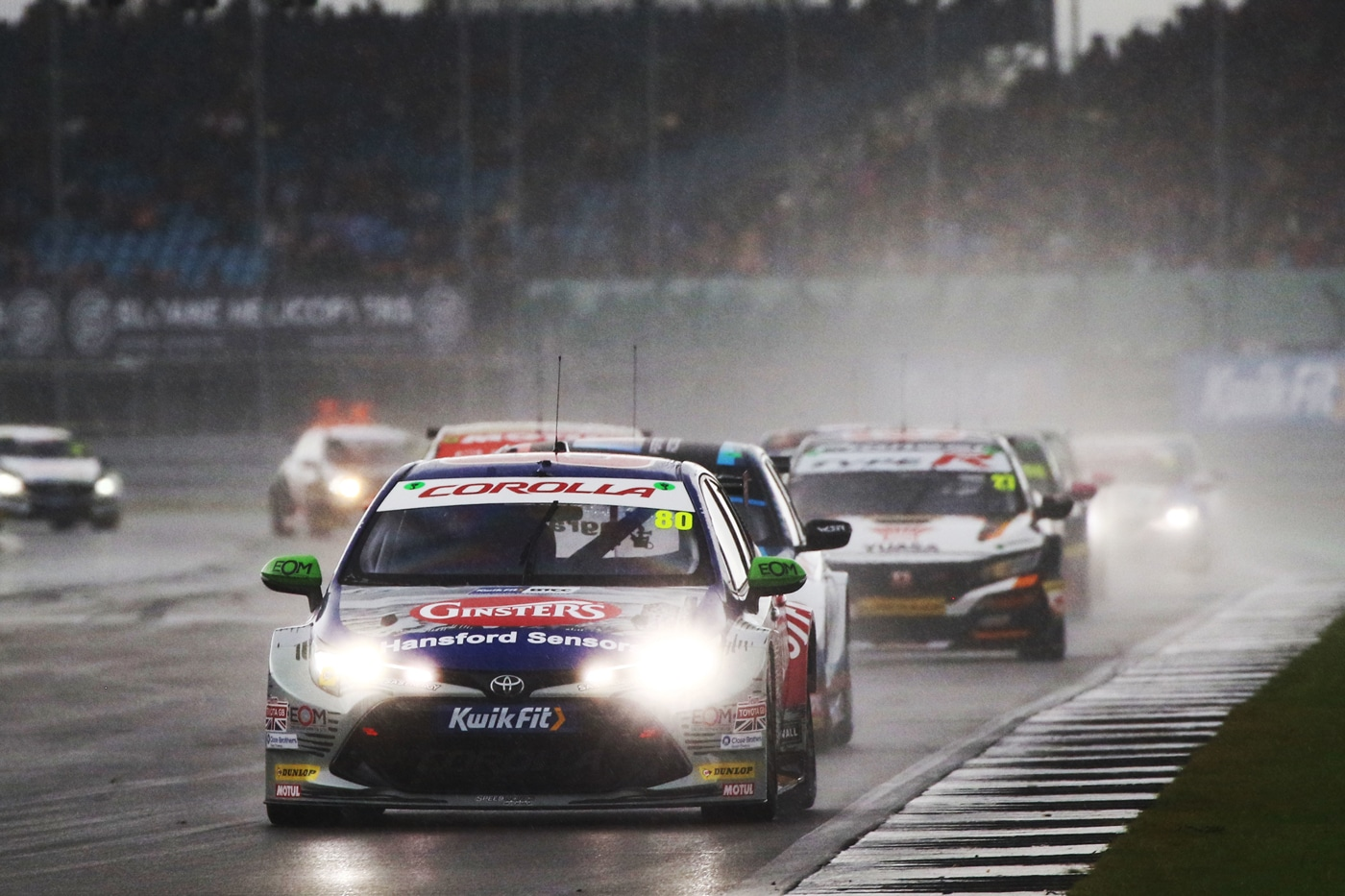 Ingram with his headlights on in front of competitors on the very wet track with low visibility